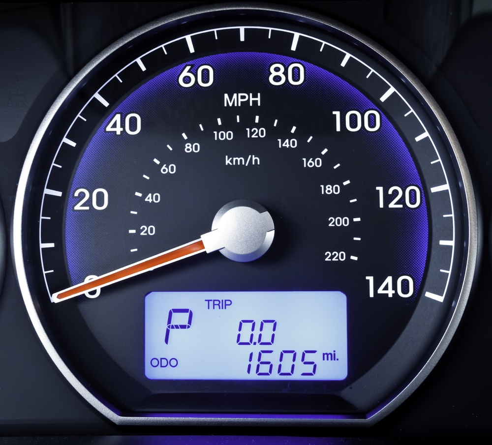 Speedometer in parked car, with LCD display of odometer and trip calculator.jpeg