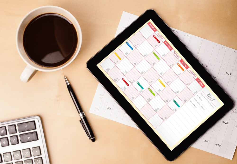 Workplace with tablet pc showing calendar and a cup of coffee on a wooden work table close-up.jpeg