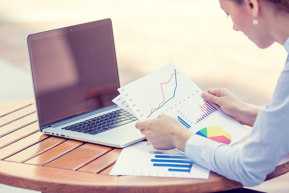 woman investment consultant analyzing company annual financial report balance sheet statement working with documents graphs. Stock market, office, tax, education concept. Hands with charts papers.jpeg