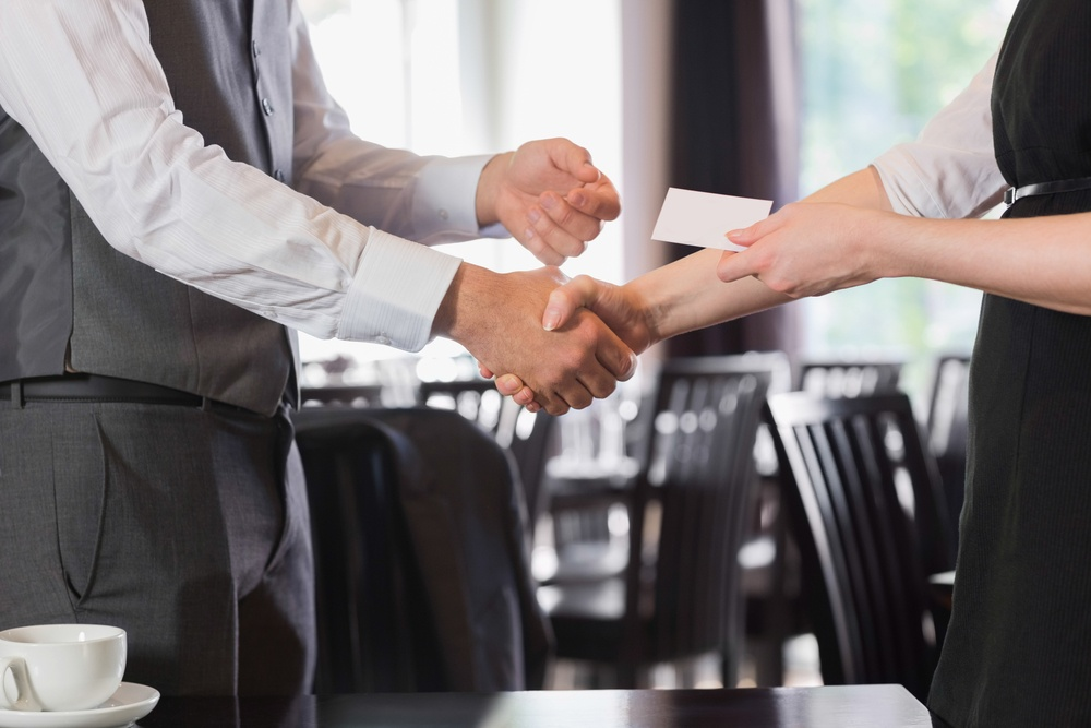 Business people shaking hands after meeting and changing cards in restaurant.jpeg